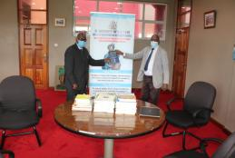 Prof. Nyamasyo (left) presents book donations to Prof. David Mungai, Director, Wangari Maathai Institute